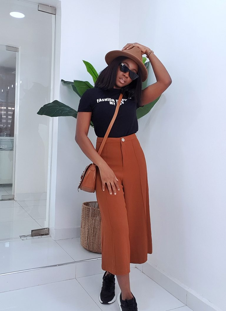 casual way to style culottes with a cross body bag, hat, t shirt and sneakers